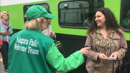 Volunteer Barbara Burrows hands out Niagara Falls tourist information to GO Transit seasonal service customers June 23, 2018