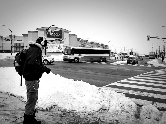 A young man prepares to cross a busy street, as a GO bus pulls out nearby.
