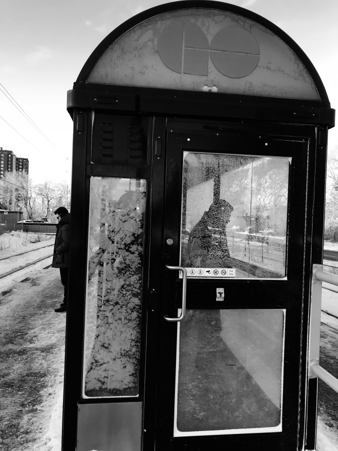 A small shelter, covered in frost, is seen with people inside. One lone man waits outside on the train platform.