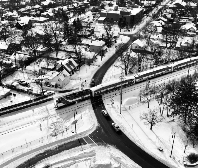 From high up in an apartment building, a GO train cuts across an intersection in Brampton. Snow covers the ground.