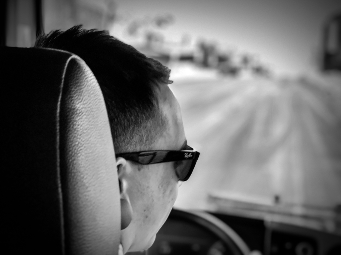 The profile of a bus driver, wearing sunglasses, is shown, with the highway ahead.