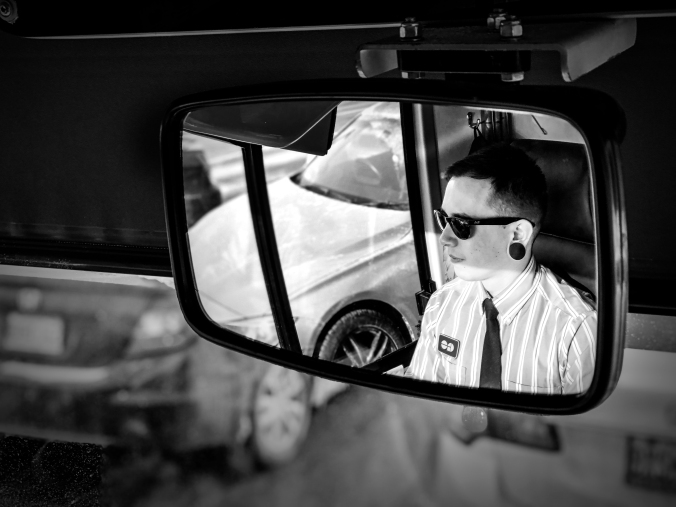 A bus driver is seen in a reflection of his mirror.