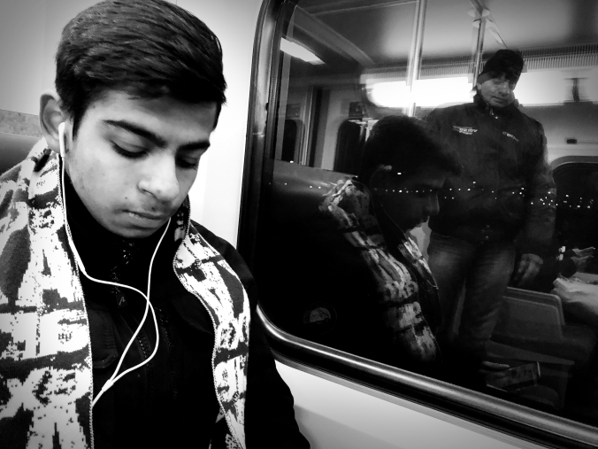 A young man sits looking at his phone while on a GO train. His image is reflected in the dark glass beyond.