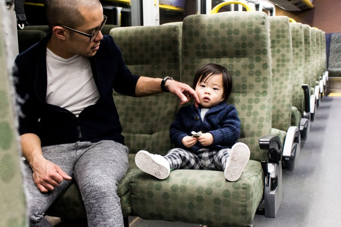 A young girl sits with her father inside the GO bus.