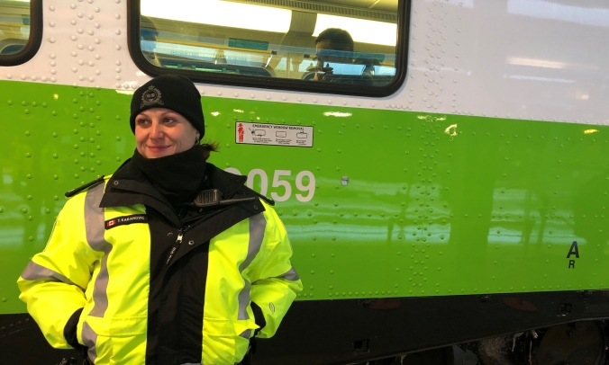 Transit officer Tihana Karanovic smiles, as she stands, hands in warm pockets, in front of a GO train.