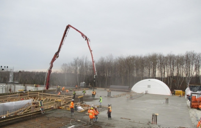 Men and equipment pour grey concrete onto the construction site.