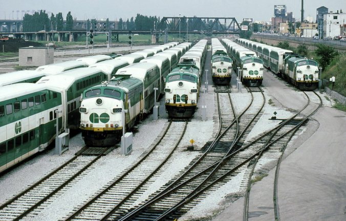 Seven lines of GO trains wait in a rail yard. There is snow on the ground.