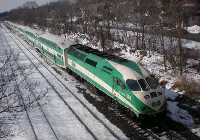 A GO train moves along a snowy landscape.