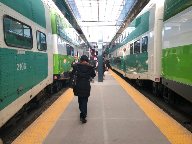 Passengers walk along a train platform, between to GO trains.