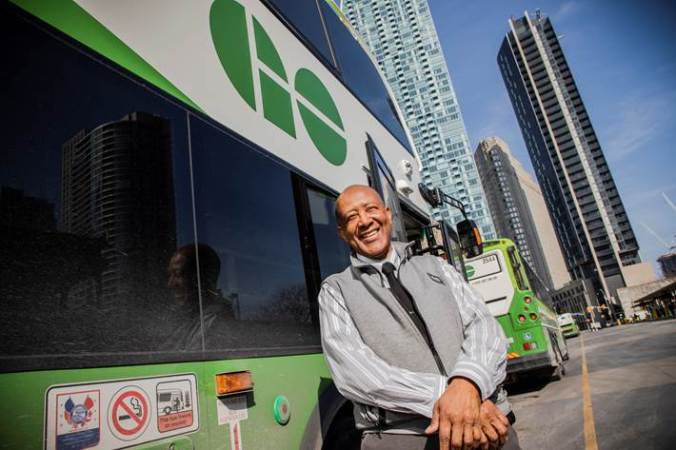 Derrick Sealy stands outside his bus on a sunny day, smiling at the camera.