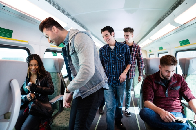 Five passengers, all smiling, take their seats on a GO train on a sunny day.