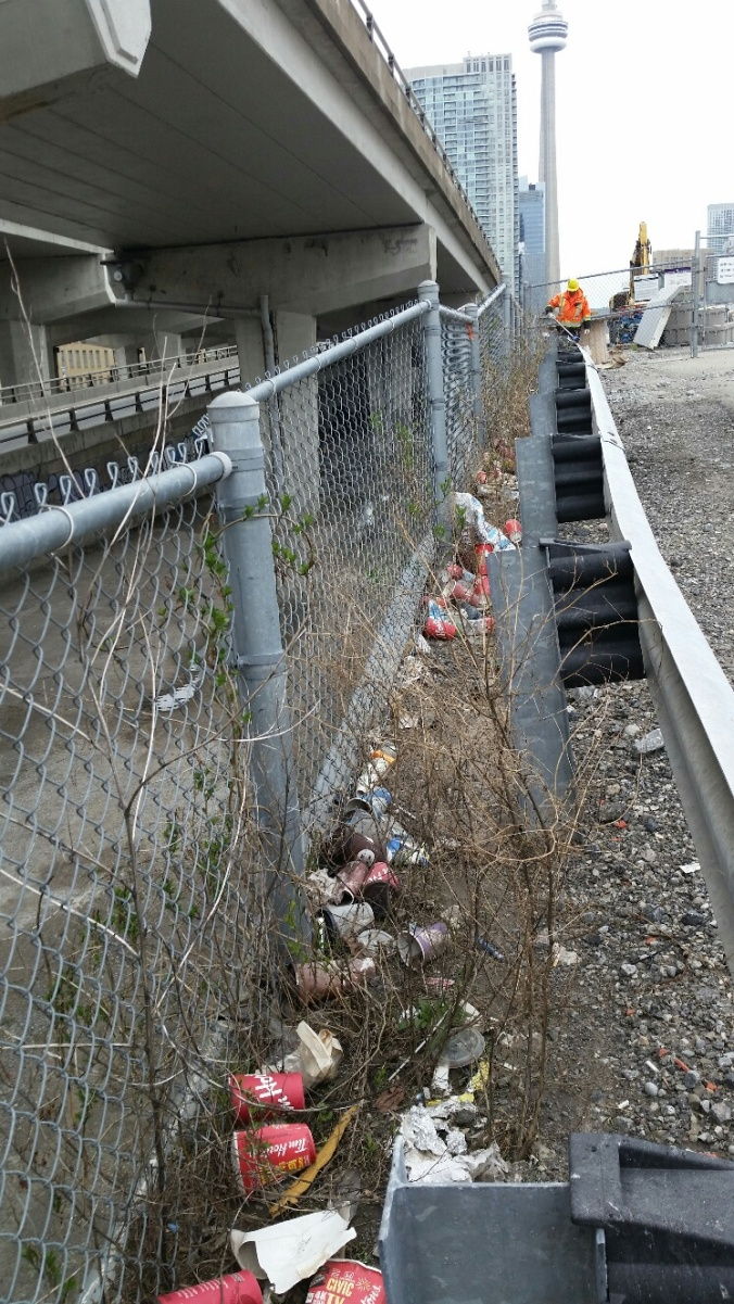 A cleaning crew member collects up garbage collecting near a fence on rail property.