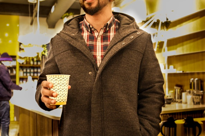 Photo of a customer holding a cup of pilot coffee.