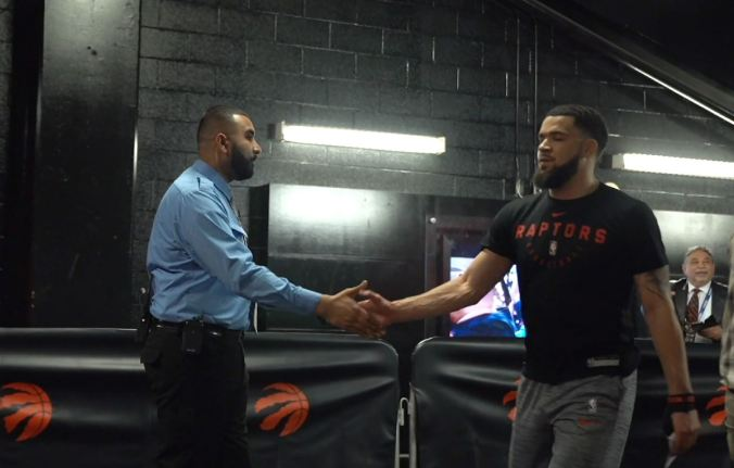 GO Transit Customer Service Ambassador Zohaib Khan at his other job as a Toronto Raptors Security guard shaking hands with Raptors point guard Fred Vanfleet