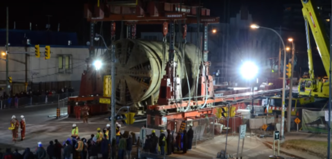Crowds gather at night to watch one of the huge tunnelling machines move into position.