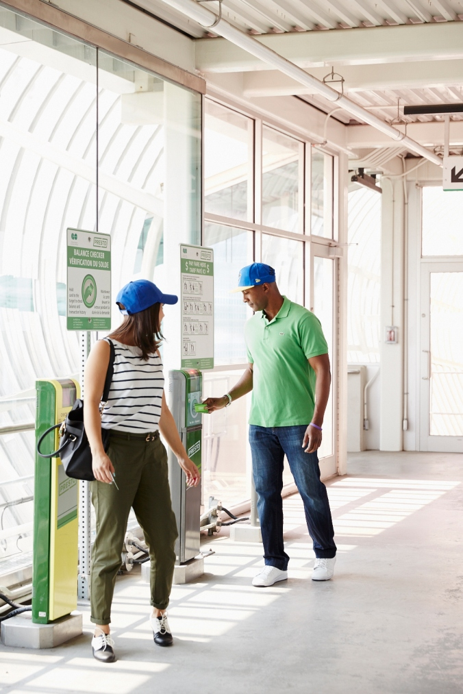 A couple walk into a GO station, as he taps his PRESTO card on a machine.