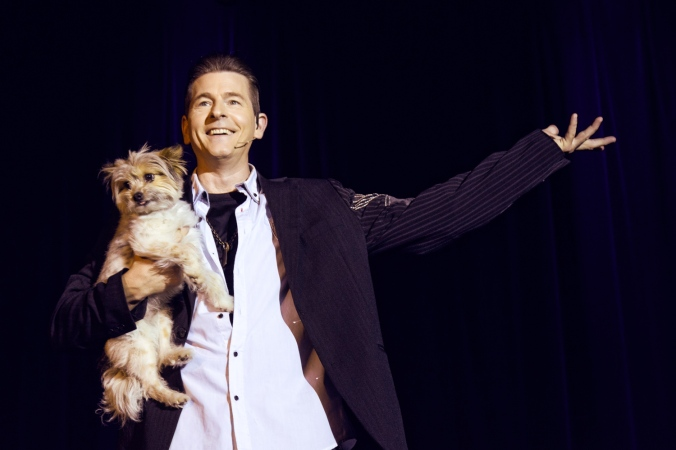 Frewin holds a small dog as he takes a bow.