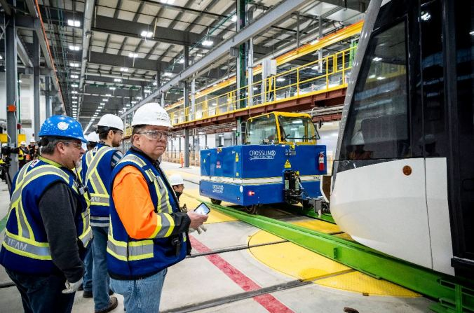 Gord Campbell is shown watching the first LRV being delivered inside the Crosstown maintenance facility.