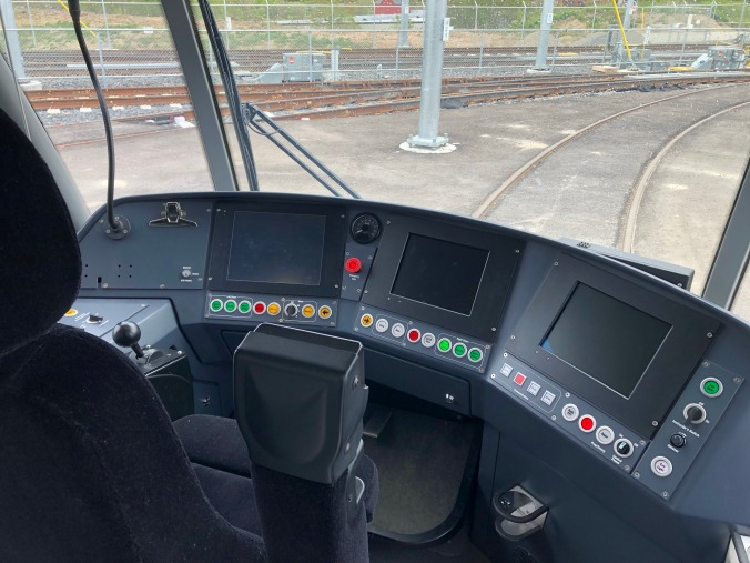 The driver's seat is shown, with three screens and plenty of buttons.