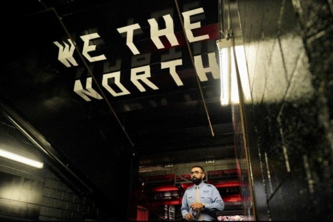 Khan walks under a large banner that reads 'We the North'.