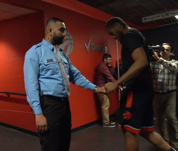 Zohaib Khan reachs to bump fists with player Kawhi Leonard, as the Raptors head to the dressing room.