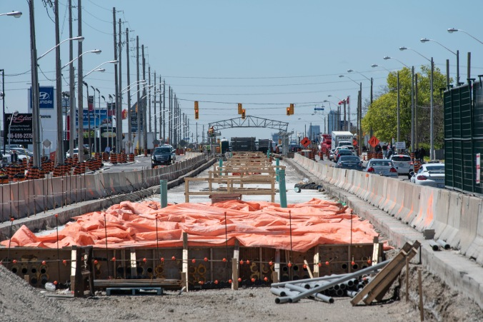 Construction material and concrete barriers line the centre position, between Eglinton Avenue East roadway.