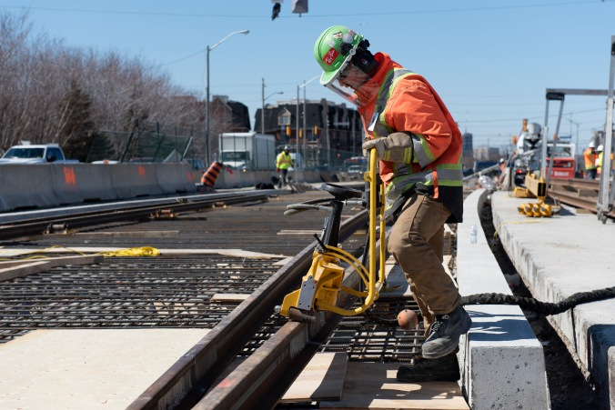 A crew meber uses a large tool to adjust a piece of track.