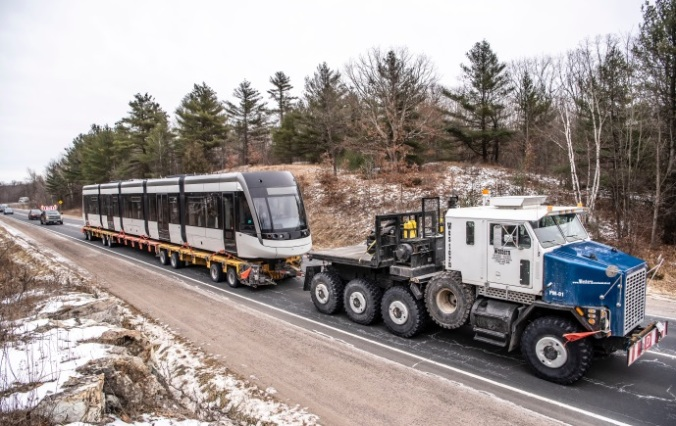 A truck hauls the LRV down a single-lane highway, as it heads toward Toronto.