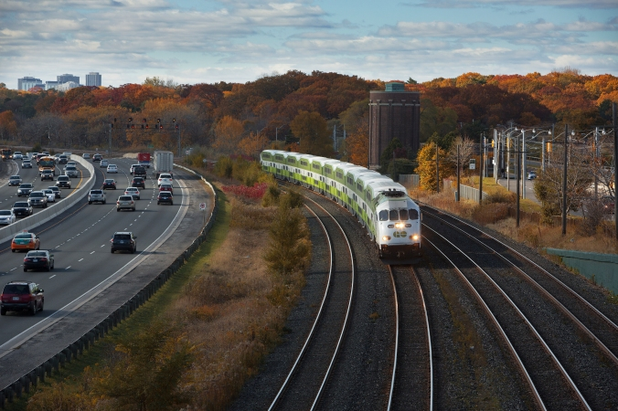 A GO train makes its way along tracks, as cars in a nearby expressway roll by.