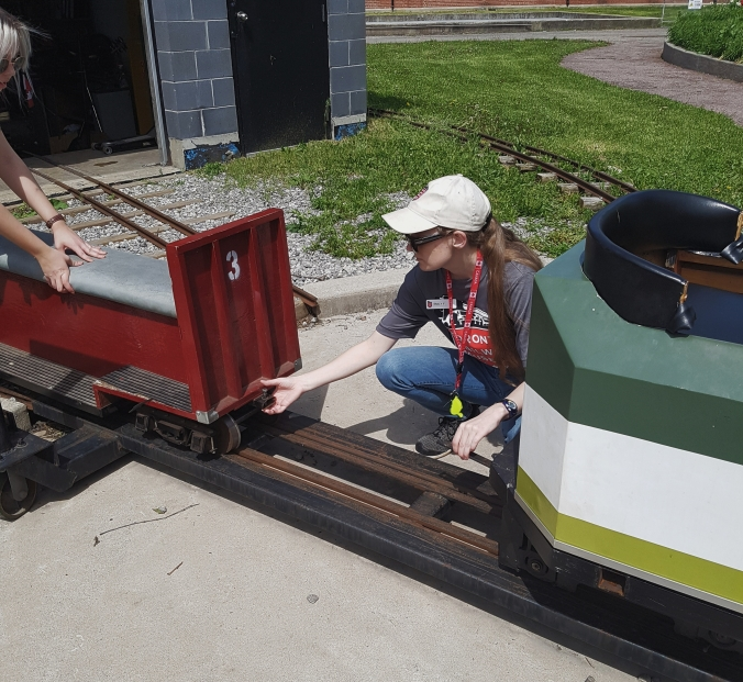 Two volunteers connect up a coach section to the engine of the mini GO train.