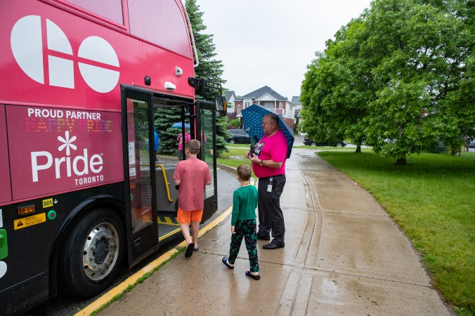 Two children walk onboard the open doors of a GO bus.