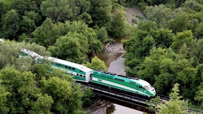 A GO train heads over a small bridge.