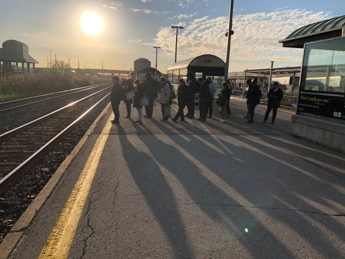 A line of customers produce long shadows on the platform, as an early day sun rises behind them.