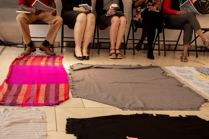 Colourful blankets are seen on the floor as participants listen to a speaker.