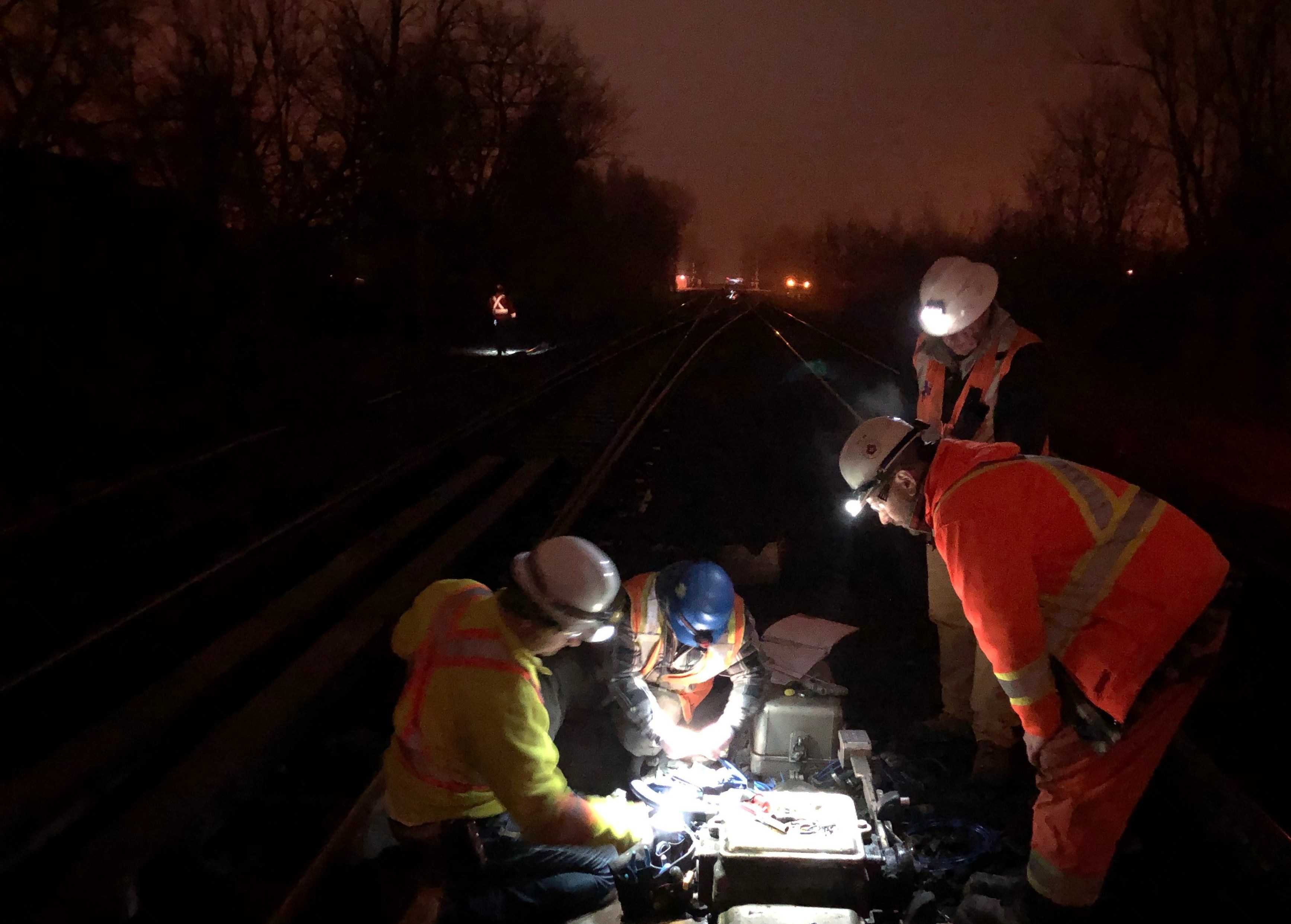 Four workmen toil away in the dark, as they peer into a piece of rail equipment.