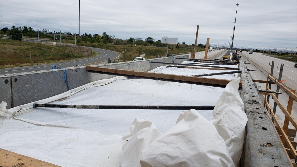 Image shows traffic flowing beside concrete work.
