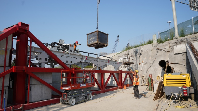 A large piece of equipment is lowered into the site.
