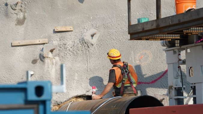 A worker looks closely at a wall of concrete, in preperation of work to come.