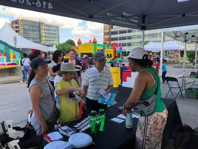 A family stops by a booth to talk to a member of the LRT communications team.
