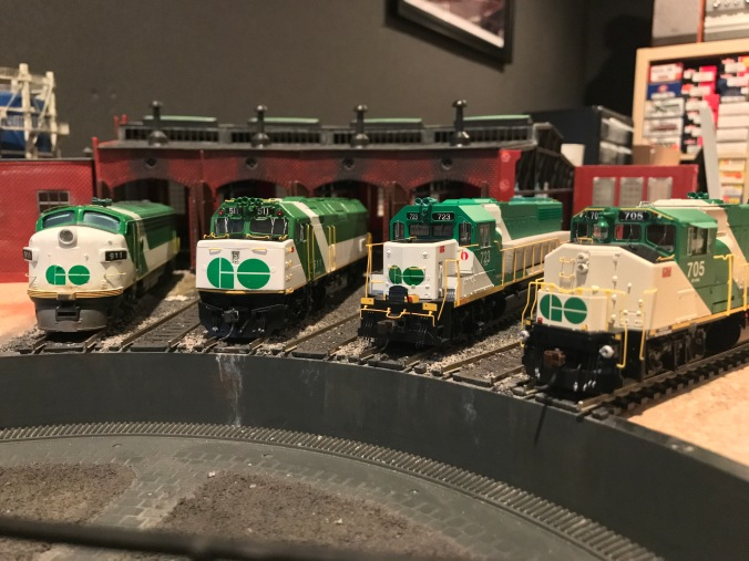 four model GO trains sit idle in the miniature rail yard.