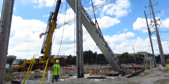 An escalator is lowered into the construction site for Science Centre Station by a giant crane.