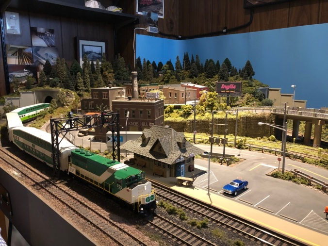 A model GO Train rounds a bend on an elaborate miniature Toronto railroad track.