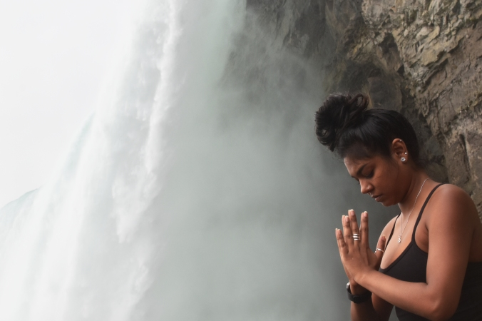 An instructor, eyes closed, meditates next to the roar of the Falls.