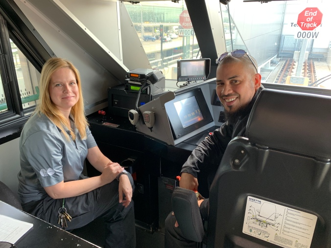 Erica Ling and Jason Simmons pose in the cab of an UP Express train.
