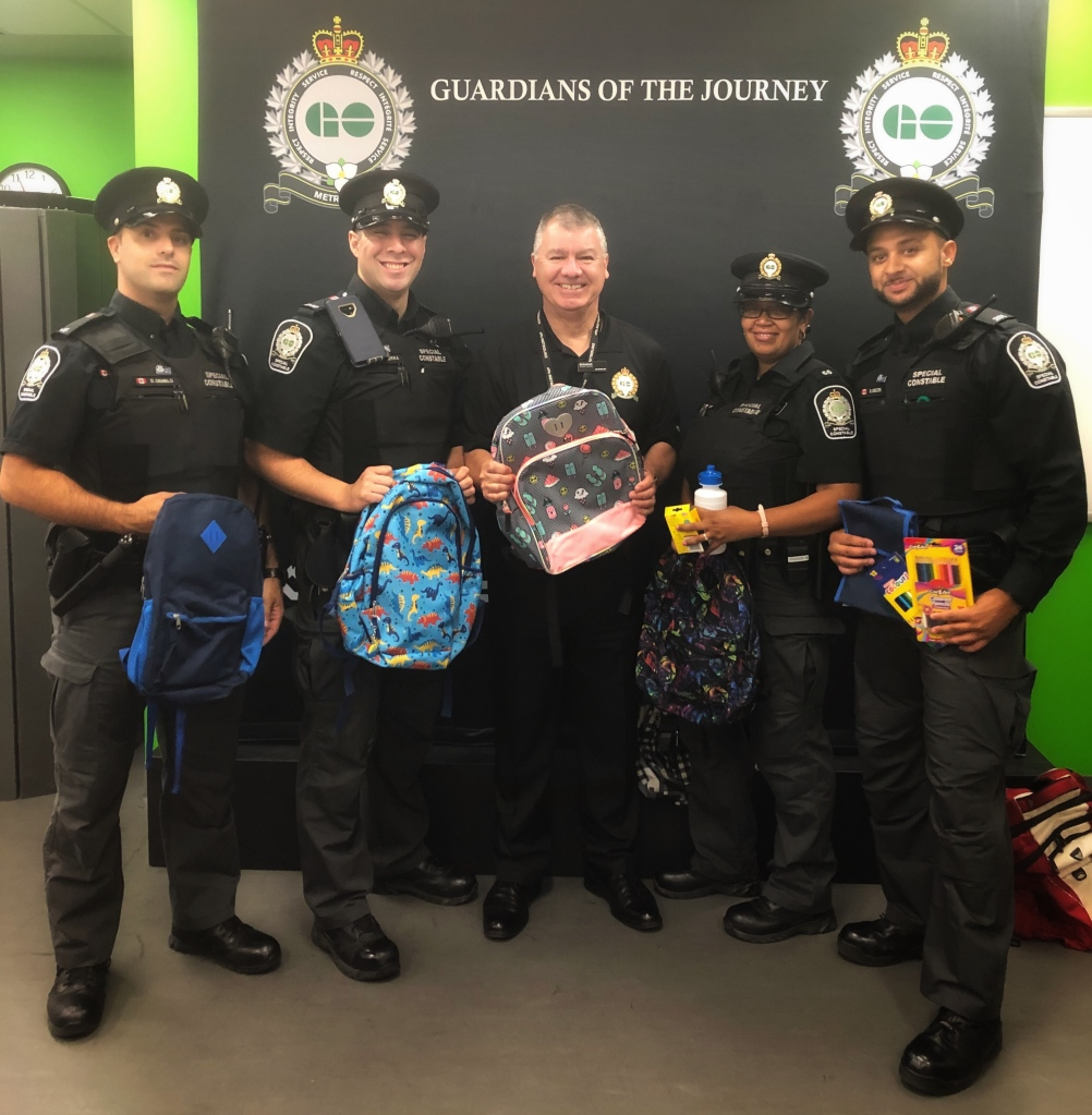 Transit safety staff line up and pose with backpacks.