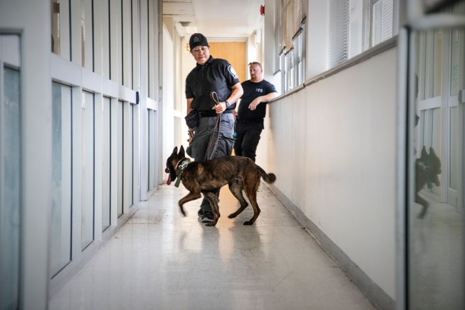 Raiden and his handler are seen patrolling a hallway.