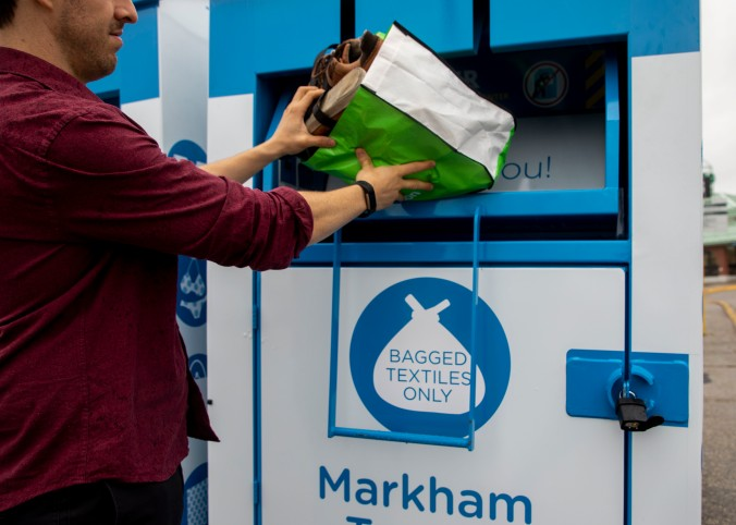 Photo of a person throwing a bag of clothes in a donation bin.
