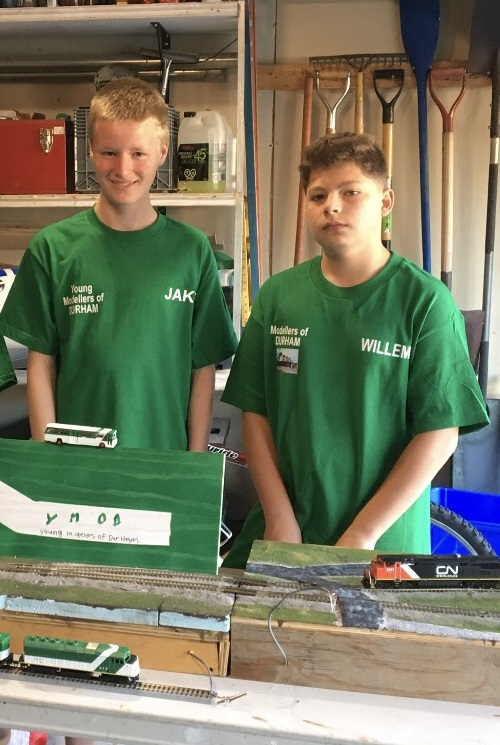 The two teens pose in front a model GO train set.