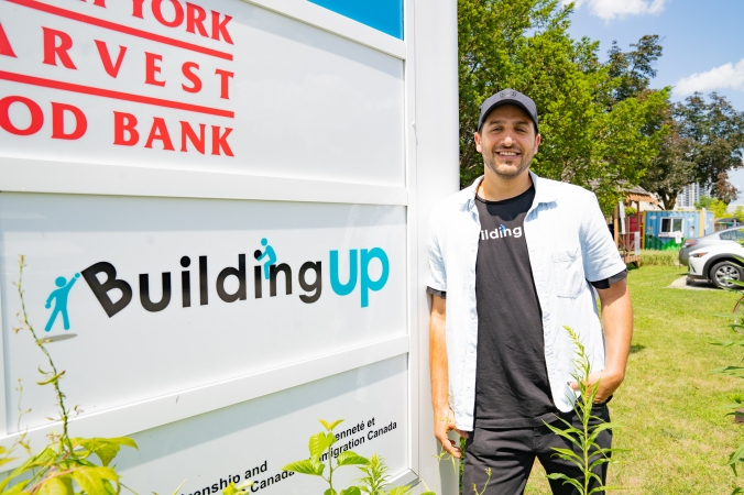 Adam Zweig from Building Up stands next to his business sign