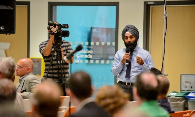 Darshpreet Bhatti stands up to answer a question before the crowd.